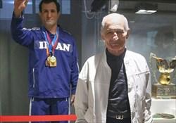 عبدالله موحد در کنار تندیس خود در موزه ورزش