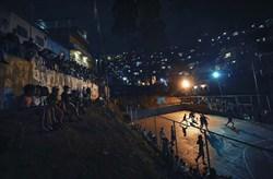 ساکنان یک محله در شهر کاراکاس، پایتخت ونزوئلا یک مسابقه بسکتبال را تماشا می کنند.